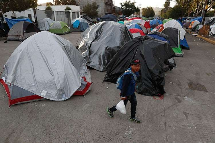 MEXICO. A migrant walks into a migrant tent camp outside the closed Benito Juarez sports complex in Tijuana, Mexico, Friday, December 14, 2018. (AP)
