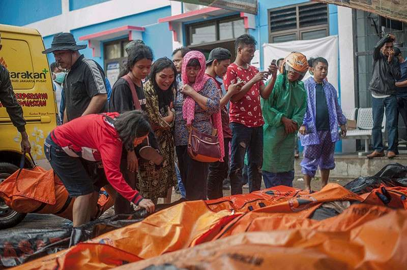 INDONESIA. In this Sunday, Dec. 23, 2018, photo, People search for relatives among the bodies of tsunami victims in Carita, Indonesia. The tsunami that hit the coasts of Indonesian islands along the Sunda Strait was not big but it was destructive. The waves smashed onto beaches in the darkness Saturday night without warning, ripping houses and hotels from their foundations in seconds and sweeping terrified concertgoers into the sea. (AP)