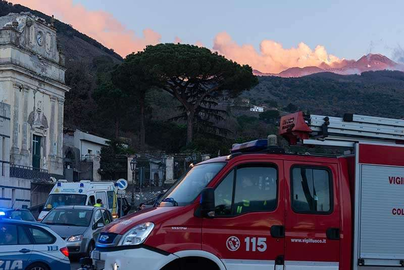 ITALY. Italian Civil protection volunteers and firefighters gather near the heavily damaged church of Maria Santissima as plumes of smoke come out the Mount Enta Volcano in Fleri, Sicily Italy, Wednesday, Dec. 26, 2018. (AP)