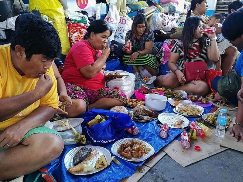 LUNCH TREAT. Fire survivors in Duljo-Fatima, Cebu City enjoy a lunch treat courtesy of senatorial aspirant Bong Go. (SunStar photo/Arni Aclao)