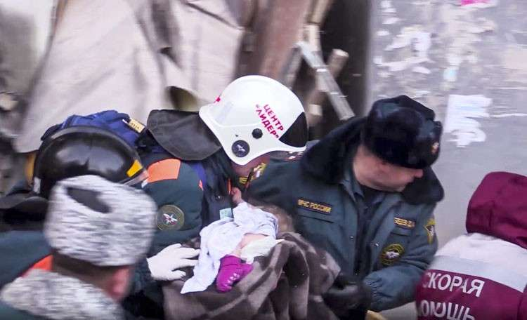 MOSCOW. This photo provided by the Russian Emergency Situations Ministry taken from television footage shows Emergency Situations employees carry a saved 10-month old baby at the scene of a collapsed section of an apartment building, in Magnitigorsk, a city of 400,000 about 1,400 kilometers (870 miles) southeast of Moscow, Russia, Tuesday, January 1, 2019.  (AP)
