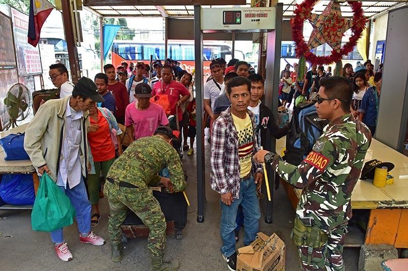 DAVAO. Gisusi pag-ayo sa mga sundalo sa Task Force Davao ang mga bagahe sa mga pasaherong manakay og bus sulod sa Davao City Overland Transport Terminal pauli sa tagsa-tagsang mga probinsiya human ang pagselebrar sa bag-ong tuig diri sa dakbayan sa Davao. (Macky Lim)