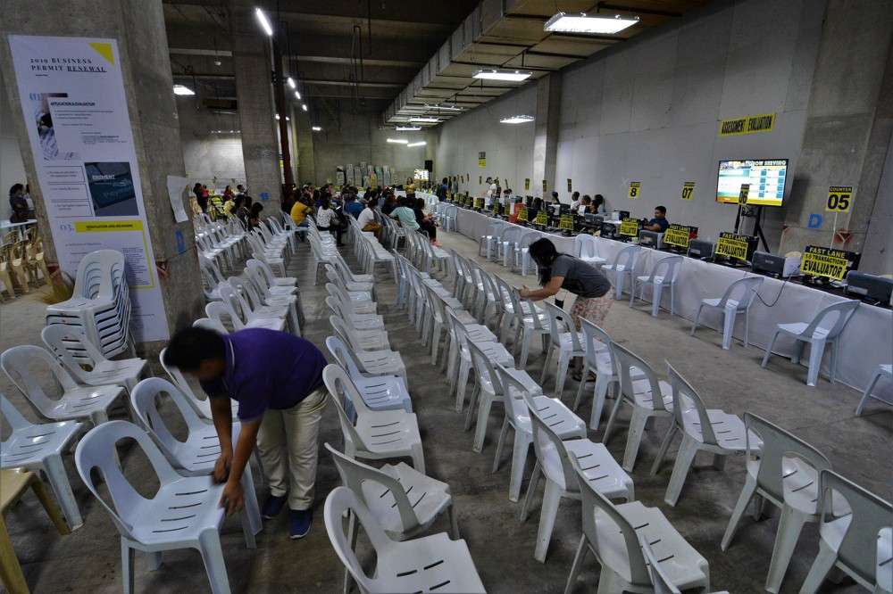 READY FOR THE BIG DAY. Employees of the Cebu City Treasurer's Office arrange the chairs meant for taxpayers who will renew their business permits at the one-stop-shop at the Robinsons Galleria Cebu. (SunStar photo / Amper Campaña)