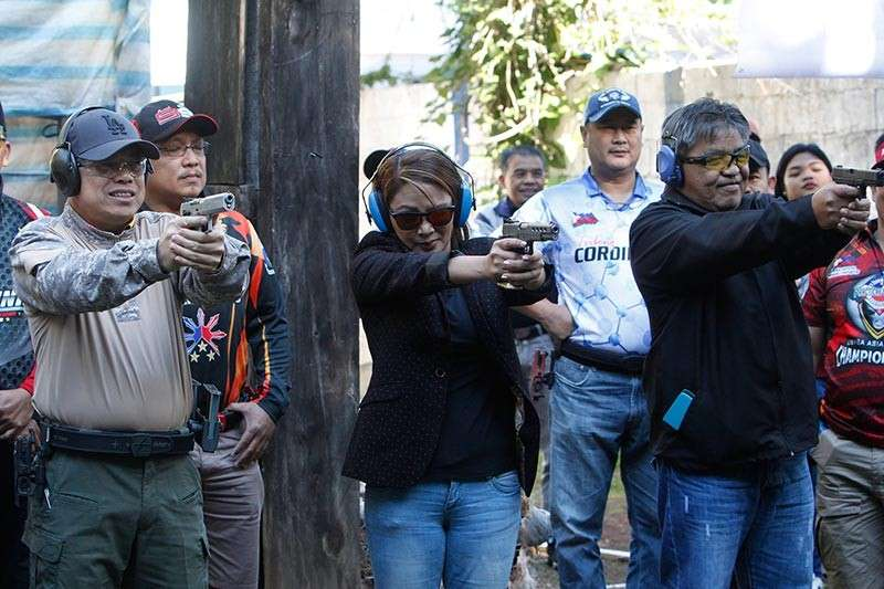 Presidential Communications Operations Office Assistant Secretary Marie Rafael leads the ceremonial shoot during the opening of the first Marie Rafael Cup on January 5 at Camp Bado Dangwa. She is joined by Mountain Province governor Bonifacio Lacwasan (right) and Chief Superintendent Rolando Nana (left). (Photo by Jean Nicole Cortes)