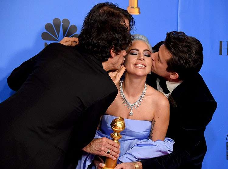 USA. Anthony Rossomando, from left, Andrew Wyatt, and Mark Ronson (right) kiss Lady Gaga (second right) as they pose in the press room with the award for best original song, motion picture for