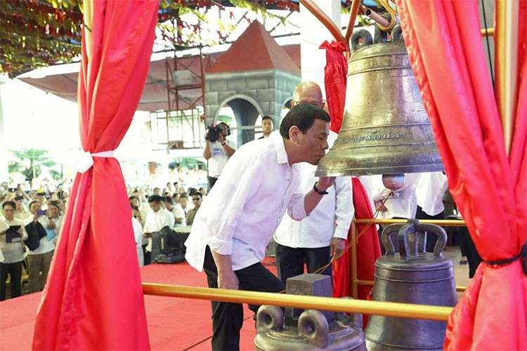 SAMAR. President Rodrigo Duterte kisses one of the Balangiga bells after witnessing the official handover of its Transfer Certificate at the Balangiga Auditorium in Eastern Samar on December 15, 2018. (Presidential Communications)