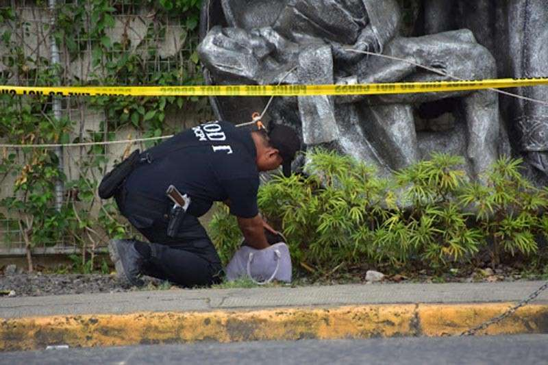 DAVAO. City Police Office Explosives and Ordinance Disposal personnel inspects a suspicious bag placed near a university's Our Lady of Compassion sculpture along Roxas Avenue, Davao City on Thursday afternoon, January 10, after a roving guard of the school alerted the authorities. However, no explosives were found inside the bag. (Macky Lim)
