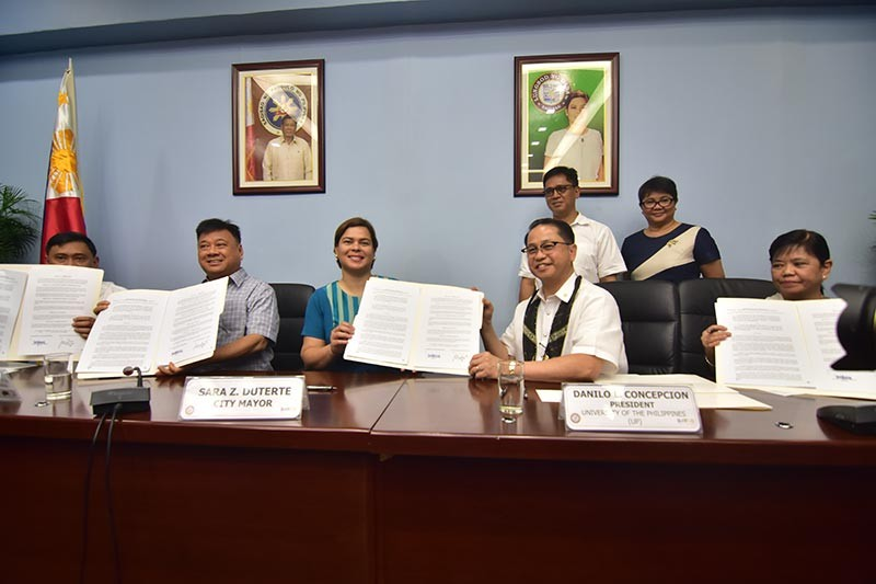 DAVAO. Davao City Mayor Sara Duterte-Carpio and University of the Philippines (UP) president Danilo Concepion hold the memorandum of agreement (MOA) for the management and operation of the Davao City-UP Sports Complex during Thursday's formal signing ceremony at the Davao City Hall Conference Room. Also in photo from left are Davao City assistant city administrator for operations lawyer Lawrence Bantiding, former congressman Isidro Ungab and UP vice-president for development Elvira Zamora. (Photo by Macky Lim)