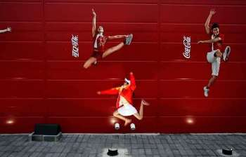 In this Aug. 20, 2008 file photo, a young girl mimics the pose of a Chinese Olympic athletes depicted in Coca-Cola advertising, at the Olympic green in Beijing. The International Life Science Institute, a group funded by the food industry, undermined China's efforts to keep obesity rates in check by overemphasizing the importance of physical activity rather than dietary restrictions, according to a new paper. (AP)