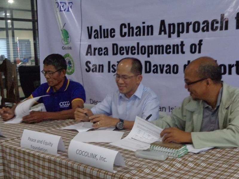 DAVAO. Dennis Omar Salvo, Partnership and Program manager of Peace and Equity Foundation (PEF) (seated, center), flanked by Mario Tipan of Laak Multipurpose Cooperative (Lampco) (left), and Bonifacio Fernandez of Cocolink, Inc. (right), sign the agreement. (Contributed Photo)