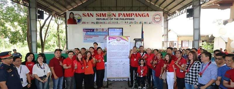 PAMPANGA. The camps of aspiring San Simon mayors Jun Punsalan and Digos Canlas flash their respective campaign signs after signing on Monday, January 14, the covenant for peaceful elections. (Chris Navarro)