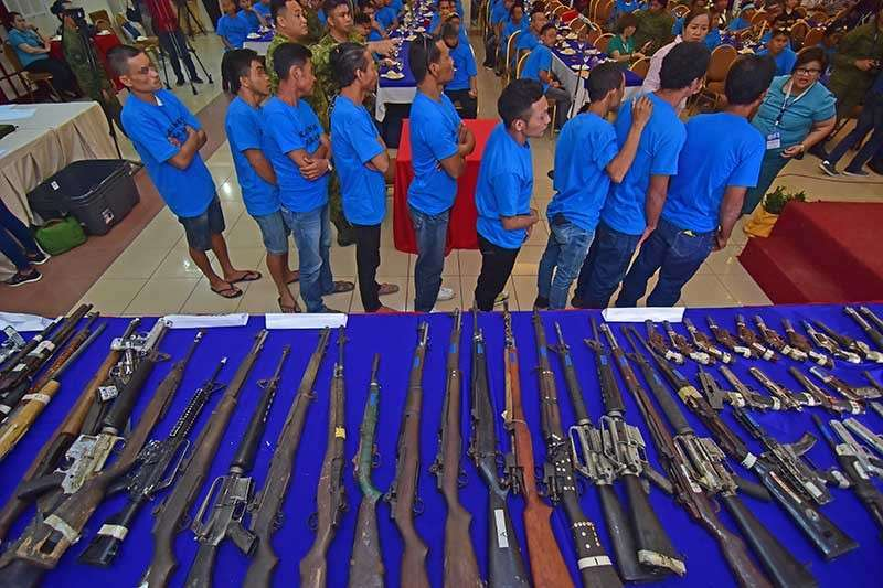 DAVAO. Former rebels line up near the table where surrendered firearms were displayed and presented during Enhanced Comprehensive Local Integration Program (E-Clip) awarding of cash assistance at the Grand Men Seng Hotel in Davao City on Monday, January 14. (Photo by Macky Lim)