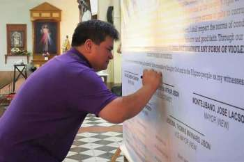 Local candidates for the May 13 elections, like Silay City Mayor Mark Golez, sign the covenant for peaceful and honest elections Sunday, January 13.