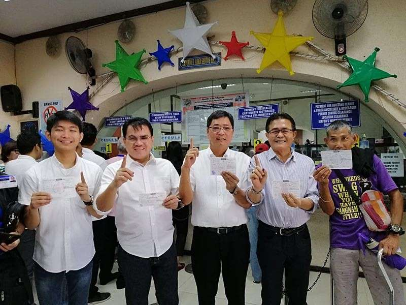 BAGUIO. (L-R) SK Federation President Gustav John Henson, Councilor Nelson Lingat, City of San Fernando Mayor Edwin Santiago and City Administrator Engr. Fernando Limbitco flash the Fernandino First sign while holding their cedulas on Monday to remind people to pay their taxes early. (Nicole Renee David)
