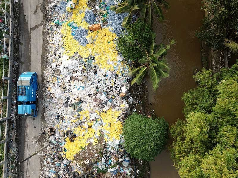 CEBU. A garbage truck passes by a pile of yellow bags containing medical waste a few meters away from the Davao City Environmental Care Inc. (DCECI) facility in Barangay Umapad, Mandaue City, Cebu. The trash pile sits next to the Butuanon River. The Mandaue City Environment and Natural Resources Office has issued DCECI a notice of violation for this and ordered the removal of the bags. (SunStar Photo/Allan Cuizon)