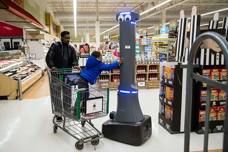 USA. William Rucker and his grandson Justice, 4, say hello to a robot named Marty as it cleans the floors at a Giant grocery store in Harrisburg, Pennsylvania, Tuesday, January 15, 2019. (AP)