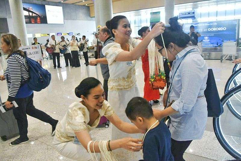 CEBUANO WARMTH. Balikbayans and tourists get a warm welcome at the Mactan-Cebu International Airport with dances, and food treats, among other. The Balik Cebu Program is a project of a number of government agencies, including the Department of Tourism, Ayala Center Cebu, and the Provincial Government. (SunStar photo / Allan Cuizon)