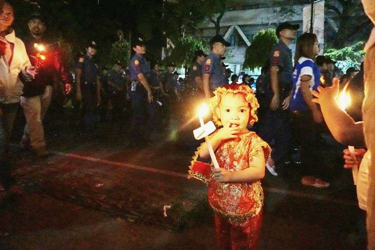 CEBU. A child dressed up as Señor Sto. Niño while holding a candle join the Walk with Mary procession early Friday, January 18. (Alex Badayos)