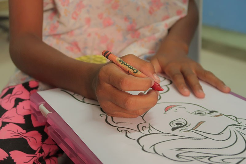 A six-year-old girl Mica coloring a cartoon at the Kean Gabriel Foundation. (Photo by Gloria Andrea Uy Mendoza)