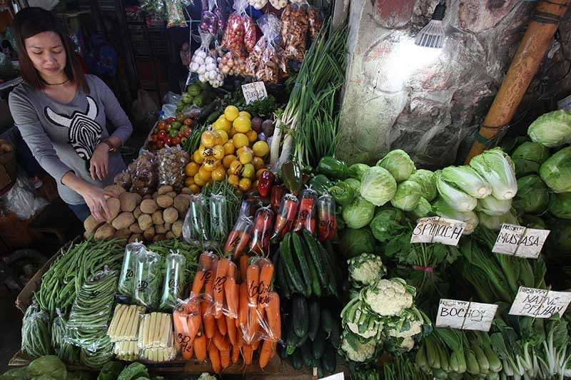 """BAGUIO. A vendor displays different highland vegetable produce. Prices and supply of vegetables remain normal despite reports of """"andap"""" or frosting. (Photo by Jean Nicole Cortes)"""