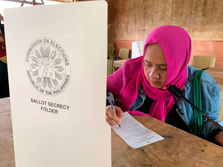 MARAWI. A Muslim woman writes down to vote in a referendum at the Marawi Sagonsongan elementary school-turned polling station in Marawi, Lanao del Sur, Monday, January 21, 2019. (AP)
