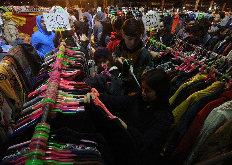 BAGUIO. Tourist and residents scour for quality jackets at the Harrison road night market as temperature continue to drop in Baguio City. The night market is favorite stop for tourists and locals. (Jean Nicole Cortes)