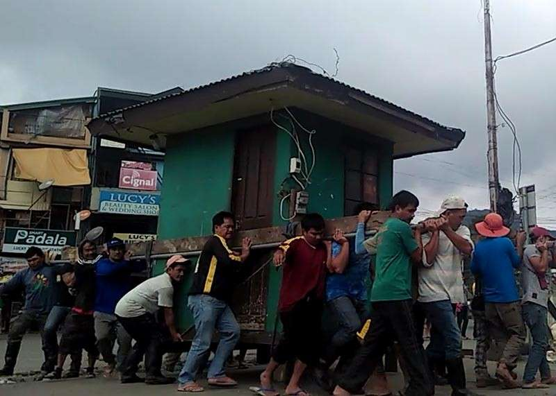 BENGUET. Volunteers carry a pay parking booth in Km. 5, La Trinidad, Benguet to pave the way for a trade fair and a carnival in the area. (Lauren Alimondo)