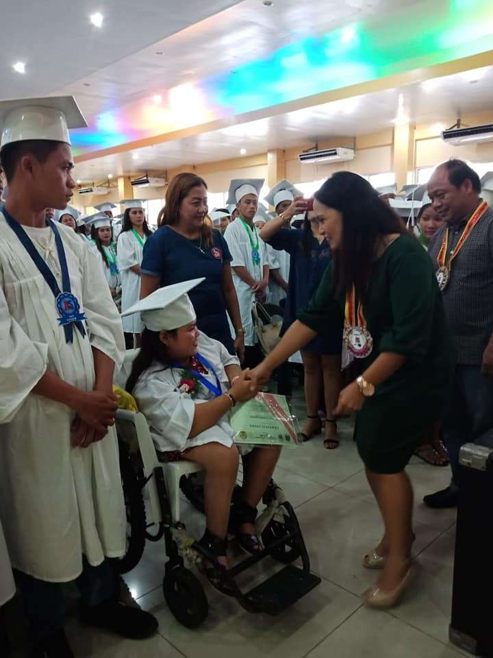 LEYTE. Marie Joy Arias, the Alternative Learning System (ALS) education program supervisor-designate of Department of Education (DepEd) in Leyte Division, congratulates a person with disability (PWD) ALS graduate from Buurauen North in Burauen, Leyte. Arias said that the support from the private sector and private individuals is important for the successful implementation of ALS education in the province. (Photo courtesy of Paz Catilogo)
