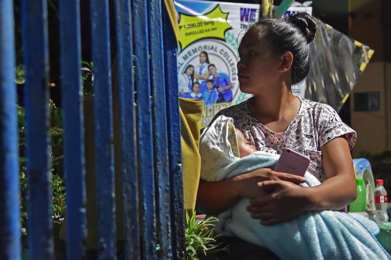 DAVAO. After hearing the first siren, a mother takes her infant to the Doña Pilar Marfori Elementary School in Don Isidro Village, Madapo Hills Barangay 5-A, Davao City on Wednesday evening, January 23, to take refuge as the water level of the Davao River continues to rise. (Photo by Macky Lim)