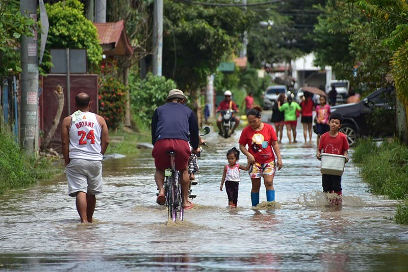 DAVAO. Residents of Jade Valley Subdivision in Davao City wade through the subdivision's flooded main street Sunday morning, January 27. (Photo by Macky Lim)