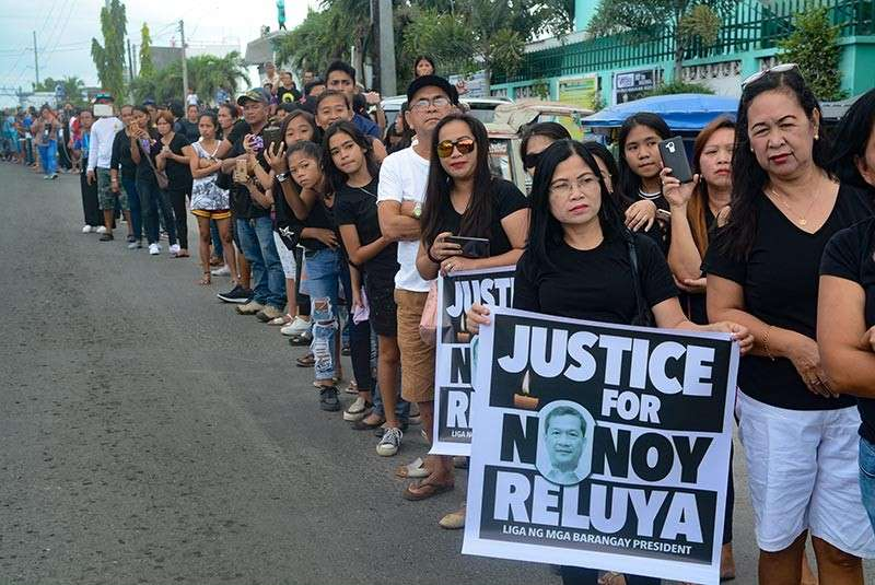 "LAST GOODBYE. Relatives, friends and supporters of the Reluyas of San Fernando town wait along the road for the arrival of the body of Municipal Councilor Ricardo""Nonoy"" Reluya, Jr. at the San Isidro Parish church in the southern town. Nonoy's wake is until Jan. 30. (SunStar photo / Arni Aclao)"