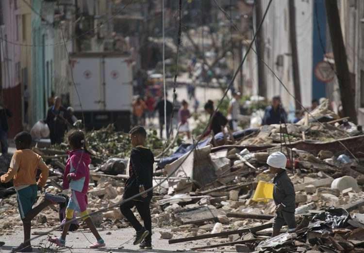 CUBA. Children walk among debris thrown up by a tornado in Havana, Cuba, Monday, January 28, 2019. A tornado and pounding rains smashed into the eastern part of Cuba's capital overnight, toppling trees, bending power poles and flinging shards of metal roofing through the air as the storm cut a path of destruction across eastern Havana. (AP)