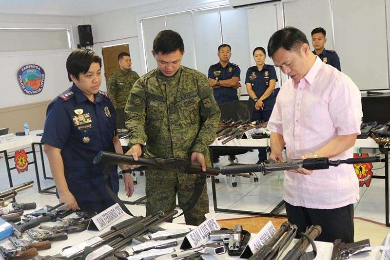 """PAMPANGA. Pampanga Provincial Police Office director Senior Superintendent Jean Fajardo, 4IB Commanding Officer Commanding Officer 1Lt. Rolly Legardo, and Provincial Election Officer Fernando Cot-om examine the firearms recovered during the implementation of """"Oplan Katok."""" (Princess Clea Arcellaz)"""