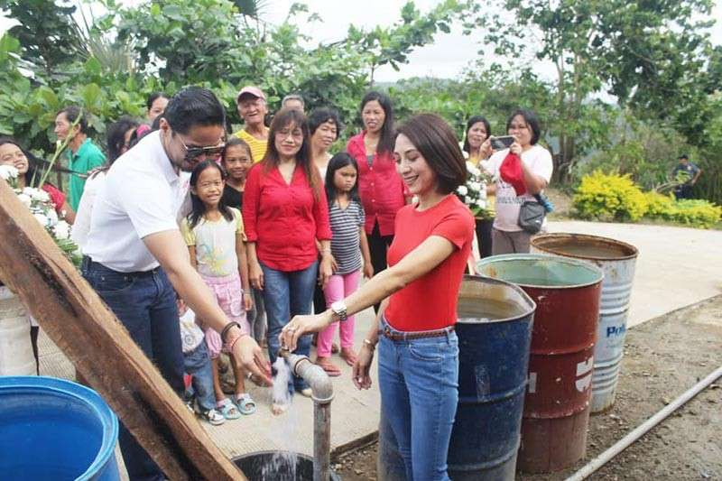 WATER WORKS.  Liloan Mayor Christina Frasco (right) and her husband Duke (left), a Cebu Port Authority commissioner, check one of 50 community faucets in Barangay Tabla. (Contributed photo)