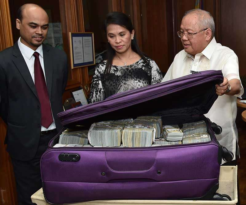 MANILA. In this March 31, 2016, file photo provided by the Bangko Sentral ng Pilipinas, from left; Second Secretary of the Bangladesh Embassy in Manila Probash Lamarong, Anti-Money Laundering Council (AMLC) Director Julia Bacay-Abad and AMLC Member Emmanuel Dooc opens a case containing US dollars that was returned by Chinese casino junket operator Kam Sin Wong to Bangladesh and Philippine AMLC officials in Manila. (AP)