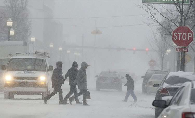 USA. People walk through a snowstorm in downtown Jackson, Michigan, Monday, January 28, 2019. (AP)