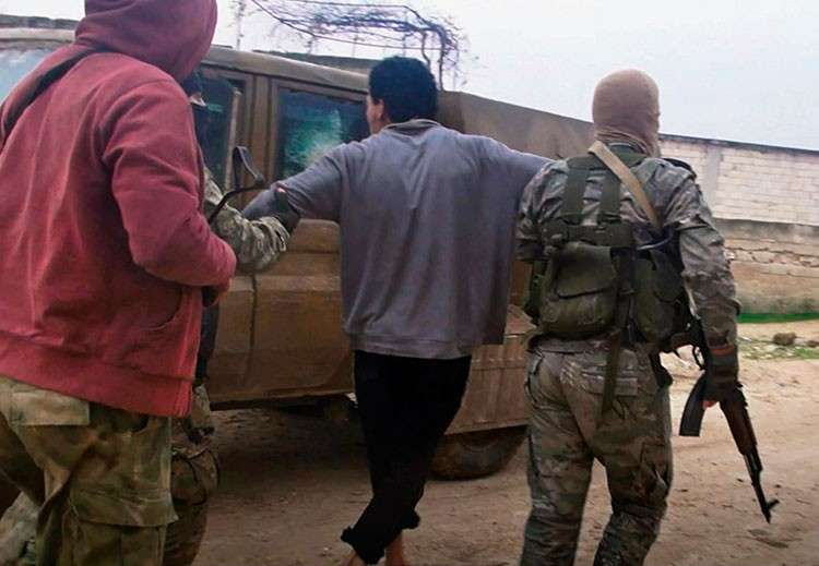 SYRIA. This December 16, 2018, file photo provided by the al-Qaeda-affiliated Ibaa News Agency purports to show al-Qaeda-linked Hayat Tahrir al-Sham, or HTS, militants detaining a member of the Islamic State group in the countryside of Idlib, Syria. (AP)