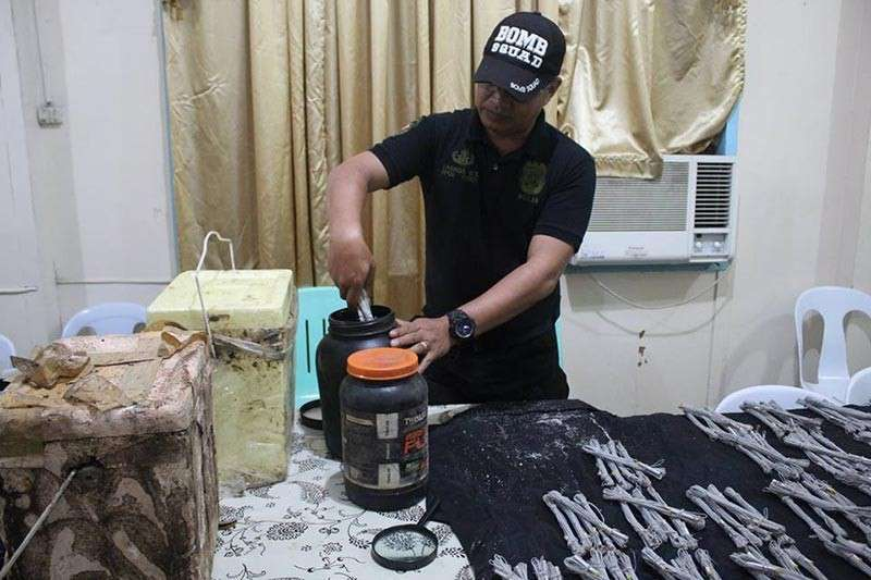 CAGAYAN DE ORO. A bomb squad personnel opens one of the two containers containing the blasting caps, a bomb-making component, found in a hinterland barangay in Butuan City. (Photo courtesy of PRO-13)
