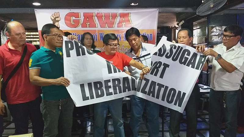 "BACOLOD. Save the Sugar Industry Movement convenor Wennie Sancho (3rd from left), along with co-convenor Hernane Braza (2nd from right) and members, leads the symbolic tearing of ""Proposed Sugar Import Liberalization"" replica at Gerald's Restobar in Bacolod Cityon Thursday, February 7. (Erwin Nicavera)"