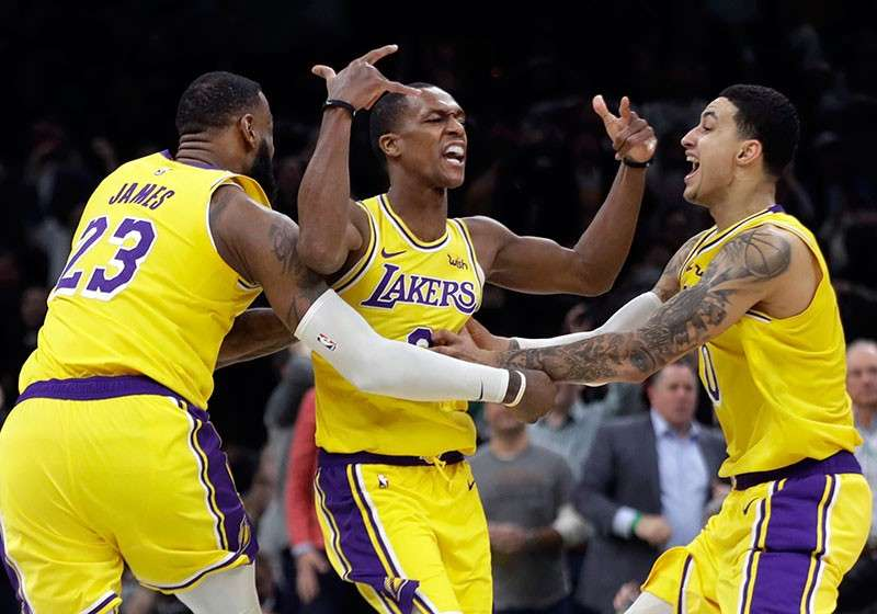 BAYANI: Ang guard sa Los Angeles Lakers nga si Rajon Rondo, tunga, nga gihangop ug giduyogan nila ni LeBron James (23) ug Kyle Kuzma (0) sa selebrasyon human kini nahimong hero sa ilang pagsulong sa Boston Celtics, 129-128, kagahapon sa nagpadayon nga NBA. (AP)