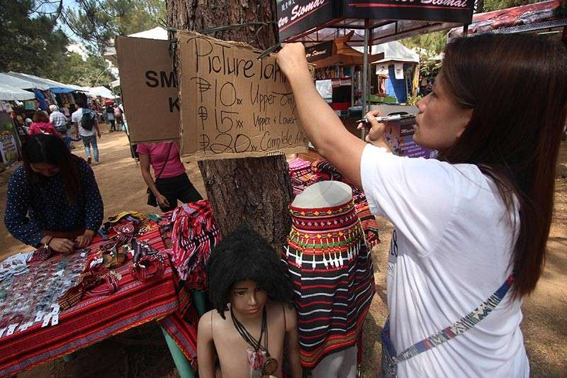 BAGUIO. Aside from selling trinkets and souvenir items, vendors at the market encounter of the Baguio Blooms offer tourists the chance to have their pictures taken in Cordillera traditional clothes for P10 to P20. (Photo by Jean Nicole Cortes)