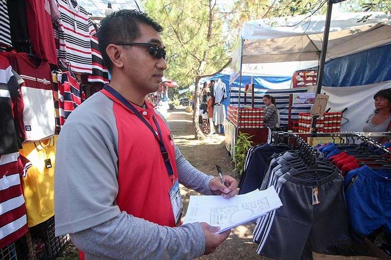 BAGUIO. Harold Halip of the Baguio City Treasurer's Office inspects the booths at the Market Encounter of the Baguio Blooms for possible violations. (Photo by Jean Nicole Cortes)
