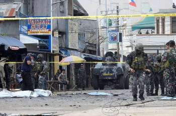 SULU. In this January 27, 2019, file photo, police investigators and soldiers attend the scene after two bombs exploded outside a Roman Catholic cathedral in Jolo, Sulu. (AP)
