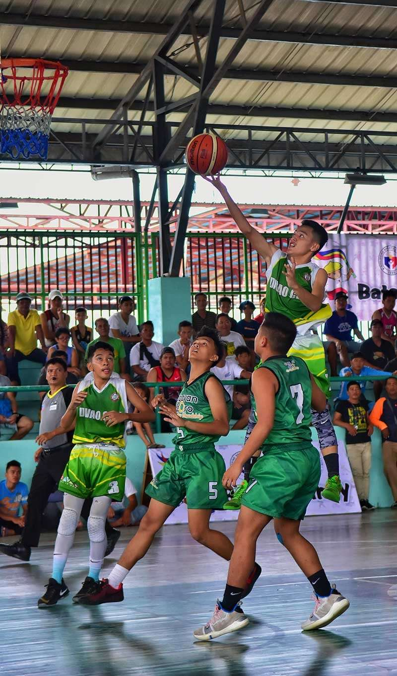 TAGUM CITY. Alexander Gabriel Tila of Davao City shoots against Cagayan de Oro City defenders in yesterday's boys basketball finals of the Batang Pinoy 2019 Mindanao Qualifying Leg held at Rotary Gym in Tagum City. (Macky Lim)