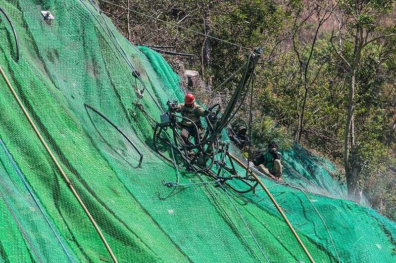 BAGUIO. Workers from Department of Public Works and Highways (DPWH) install rock nets along Kennon Road to ensure safety of travelers. The highway will be temporarily opened for one lane this week. (Photo by Jean Nicole Cortes)