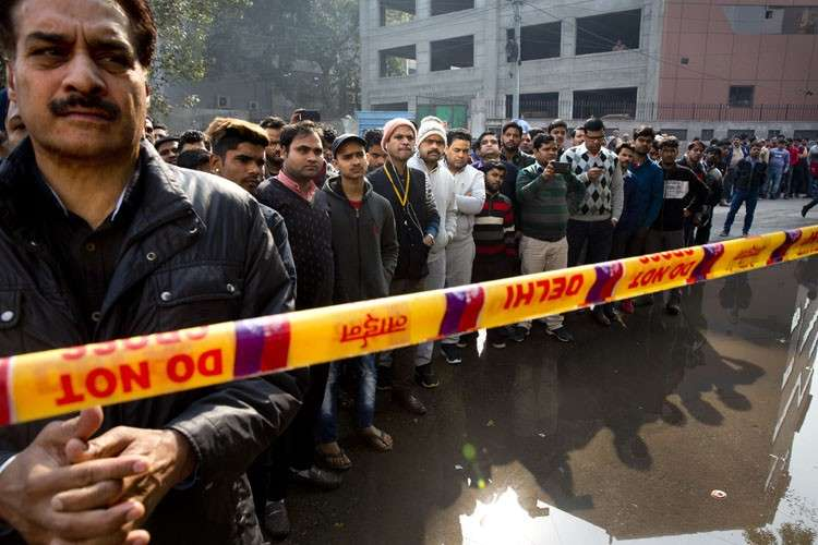 INDIA. Onlookers gather after an early morning fire at a hotel killed more than a dozen people in the Karol Bagh neighborhood of New Delhi, India, Tuesday, February 12. (AP)