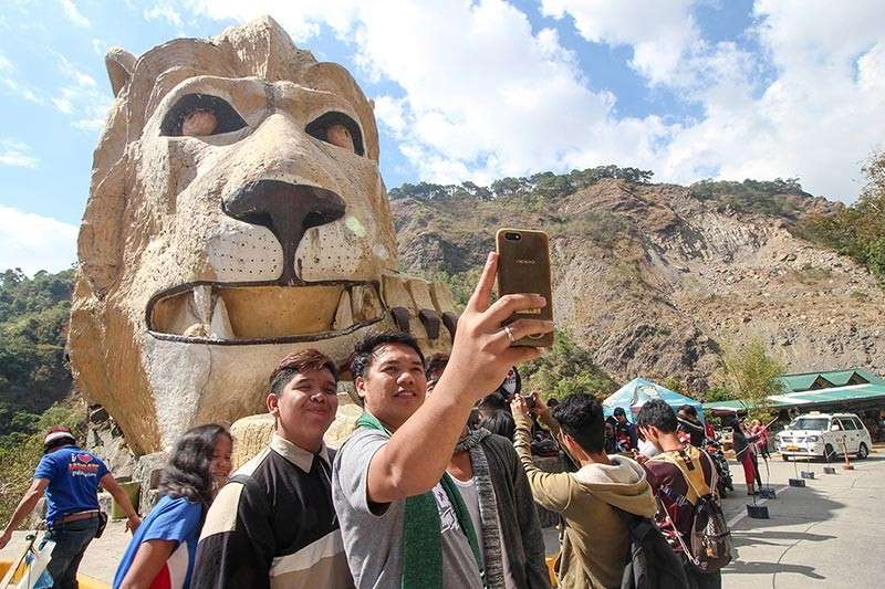 BAGUIO. Tourists take photographs at the Lion's Head along Kennon Road. Despite the road closure, tourists may enter Kennon Road to pay a short visit to the iconic structure but could not exit through the highway since road rehabilitation is still ongoing. (Photo by Jean Nicole Cortes)