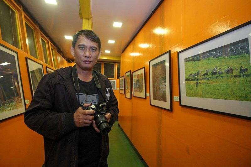 BAGUIO. Randy Nimer, a self-taught artist from Pozorrubio, Pangasinan displays 23 works depicting everyday life from the perspective of his lens. His artworks are on display at the Tam-awan Ugnayan Gallery. (Photo by Jean Nicole Cortes)