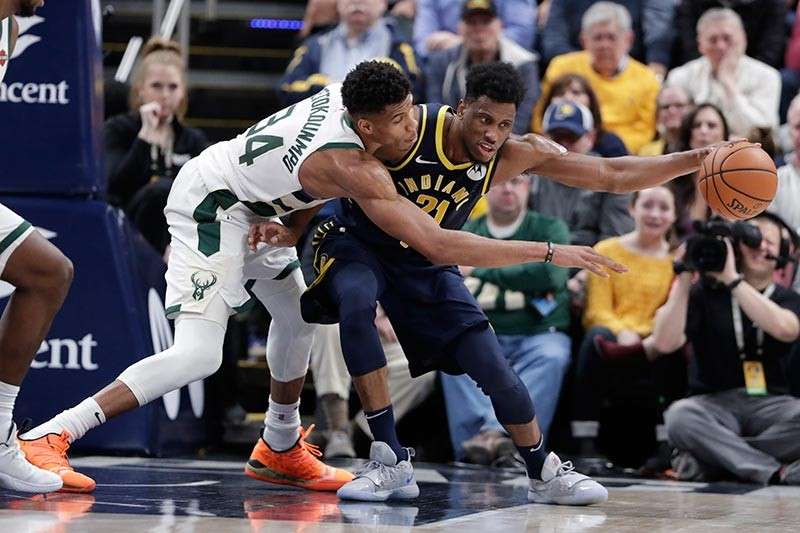 USA. Milwaukee Bucks forward Giannis Antetokounmpo (34) defends against Indiana Pacers forward Thaddeus Young (21) during the second half of an NBA basketball game in Indianapolis, Wednesday, February 13. The Bucks defeated the Pacers 106-97. (AP Photo)