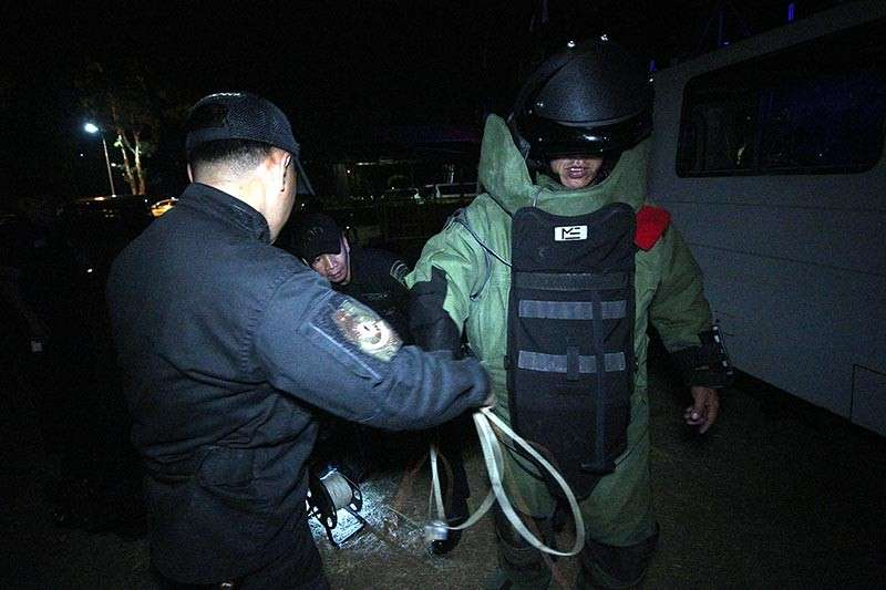 BAGUIO. Officers from the K9 unit and the Explosives Ordnance Disposal Unit of the Police Regional Office Cordillera (PRO-COR) suit up for the bomb threat simulation exercise held at the night market along Harrison Road. The bomb suit which costs P2 million was donated by the United States. (Photo by Jean Nicole Cortes)